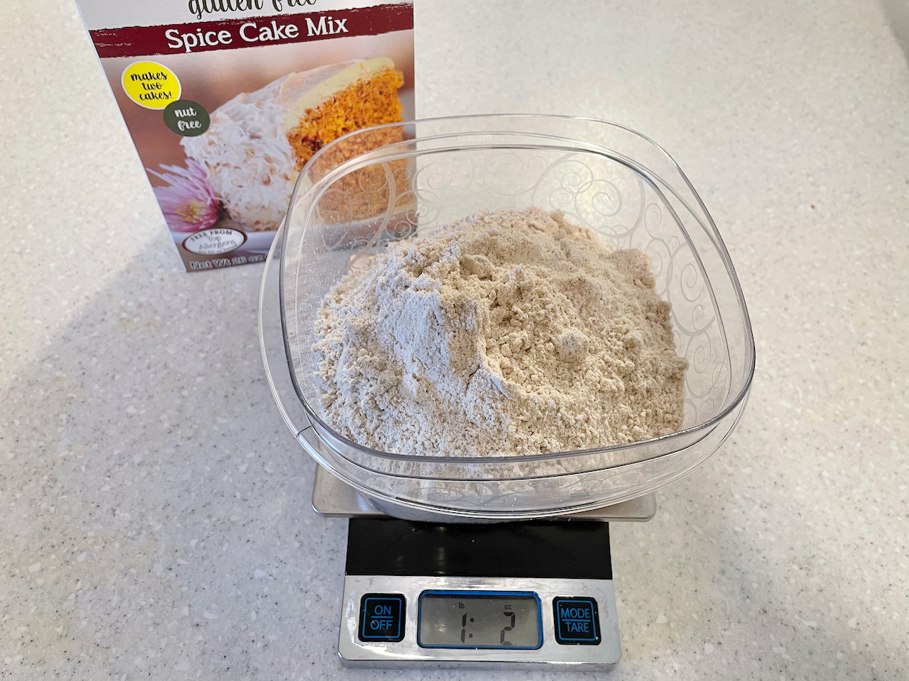 Cake mix being weighed on a food scale reading 1 pound, 2 ounces and a spice cake mix box behind it.