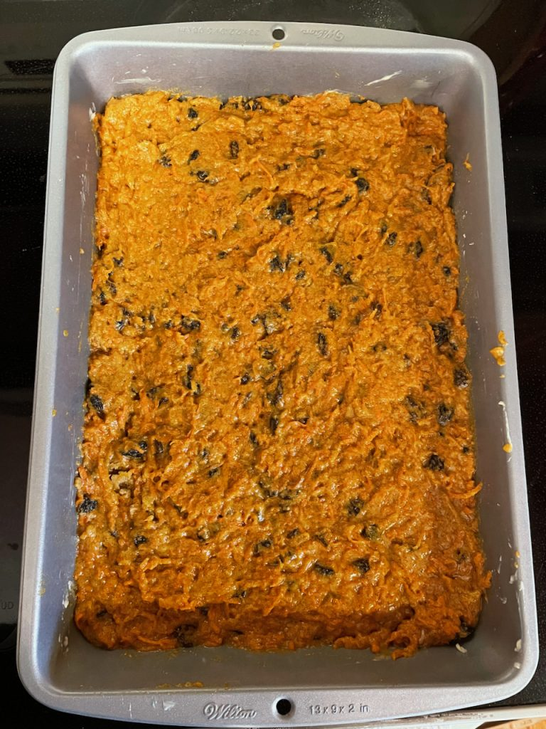 Orange colored crust with shredded carrots and raisins pressed into the bottom of a metal pan.
