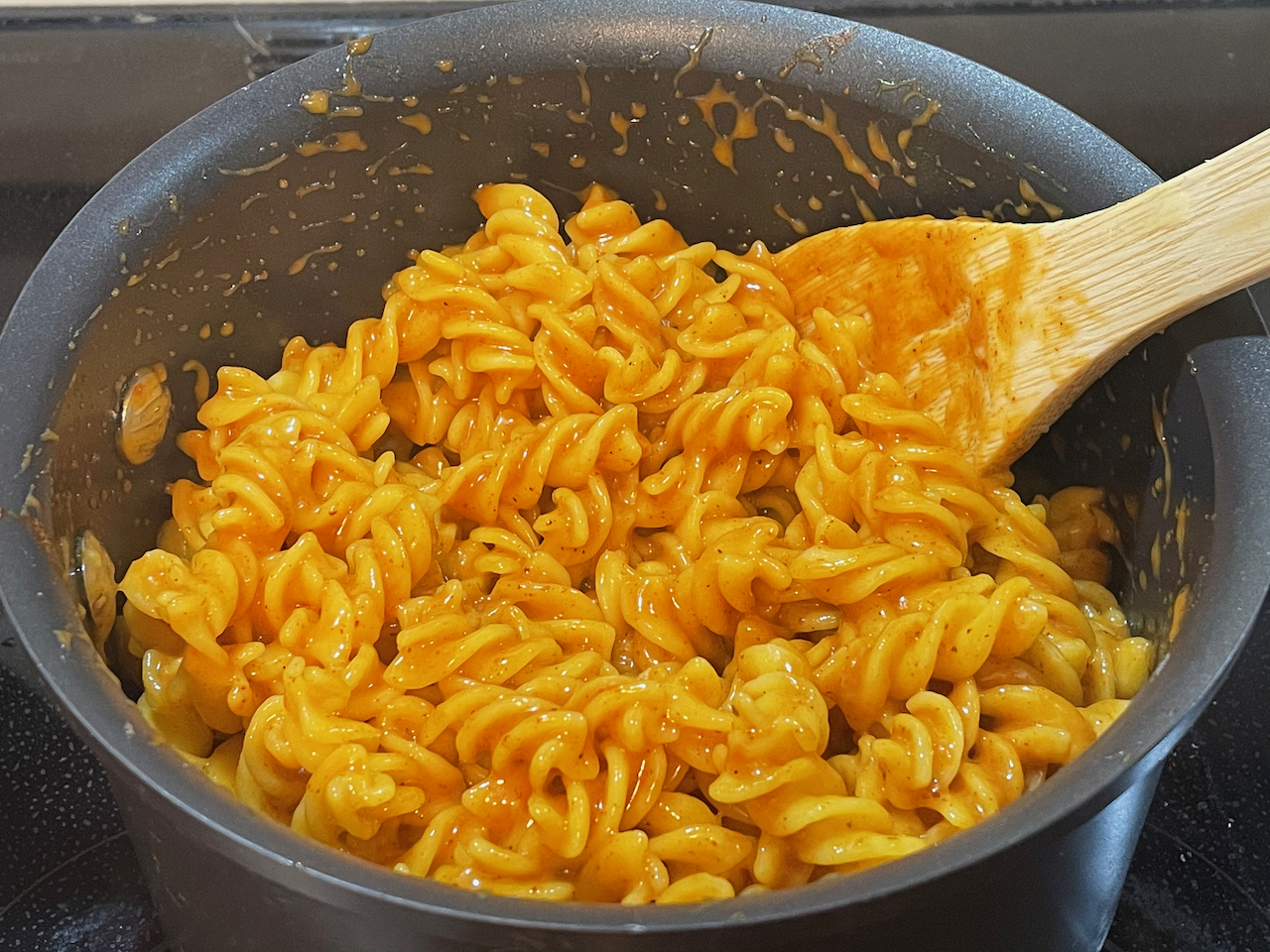 A pot of fusilli noodles coated in an orange colored sauce.